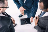 group of businessmen looking at tablet