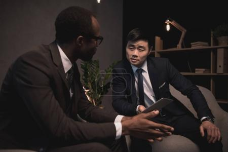Photo for Successful multiethic businessmen having conversation in dark room - Royalty Free Image