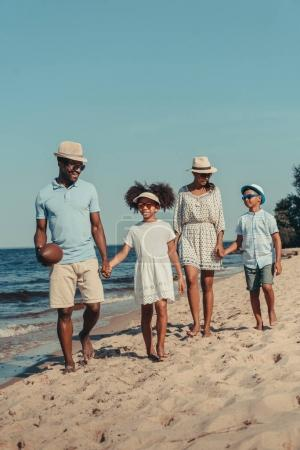 Photo for Happy african american family walking together on sandy beach - Royalty Free Image