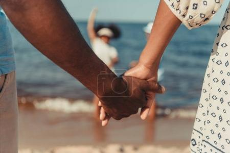 Photo for Close-up partial view of african american couple holding hands while standing at seaside - Royalty Free Image
