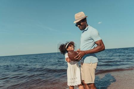 Photo for Happy african american father and daughter holding rugby ball on beach - Royalty Free Image