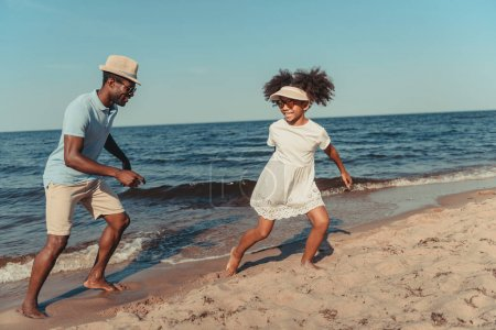 Photo for Happy african american father and daughter wearing sunglasses having fun while playing together on sandy beach - Royalty Free Image