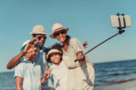 Photo for Happy african american family taking selfie with smartphone at seaside - Royalty Free Image