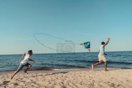 Photo pour Heureux père et fils afro-américain jouer avec cerf-volant et courir sur la plage de sable - image libre de droit