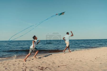 Photo for Happy african american father and son playing with kite on sandy beach - Royalty Free Image