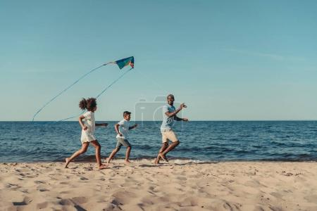 Photo for Happy african american father and kids playing with kite on beach - Royalty Free Image