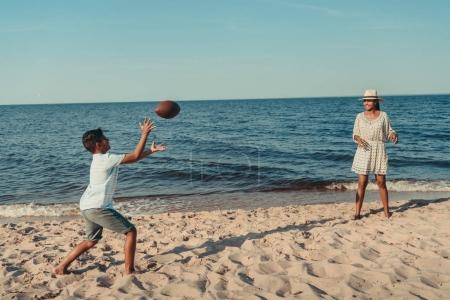 mother and son playing with ball on beach
