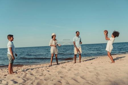 family playing with ball on beach