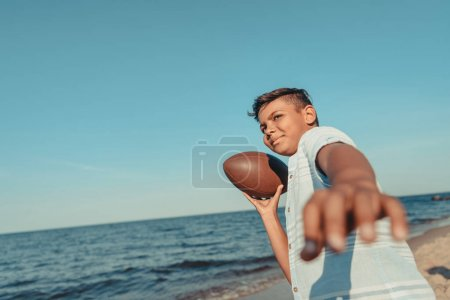 african american child with ball on beach