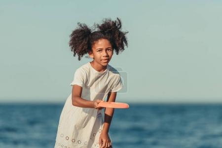 Photo pour Jolie fille afro-américaine jouer frisbee et en regardant la caméra sur la plage - image libre de droit