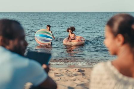 Foto de Tiro cortado de padres sentado en la playa mientras que lindo los niños jugando en el mar - Imagen libre de derechos