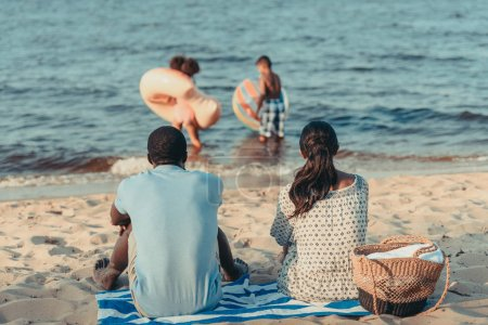 Photo for Back view of african american parents looking at kids playing in sea - Royalty Free Image