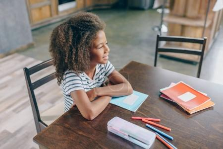 Little girl with school supplies at table