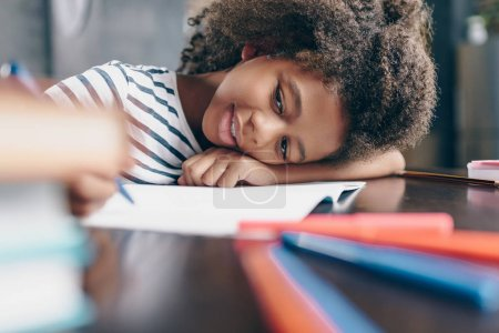 Photo for Tired little girl sitting at the table, with her head on her arm, writing in her notebook - Royalty Free Image