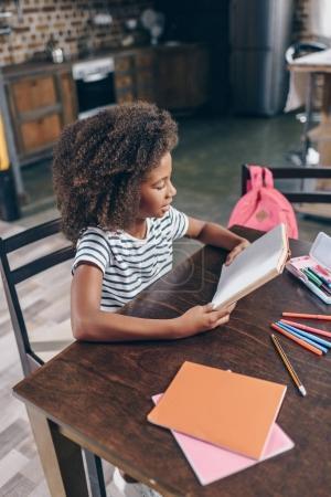 Photo pour Petite fille lisant un livre à la table de la cuisine - image libre de droit