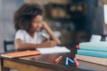 Photo pour Plan flou de la petite fille écrivant à son carnet de notes à la table de cuisine avec des fournitures scolaires en évidence . - image libre de droit