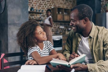 Photo pour Père et fille, lire un livre ensemble à la table de la cuisine - image libre de droit