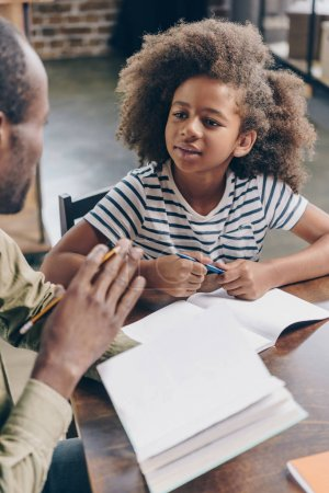 Photo for Little girl with notebook listening to her father explaining the textbook. - Royalty Free Image