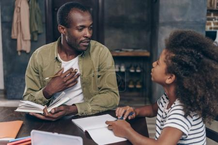 Father helping daughter do homework
