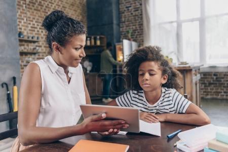 Mother showing girl digital tablet