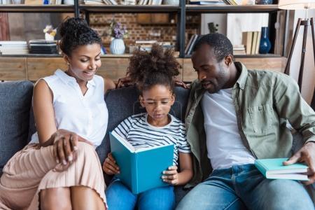 Photo pour Petite fille lisant un livre avec ses parents assis sur un canapé à côté d'elle . - image libre de droit