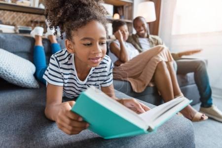 Photo pour Petite fille allongée sur un canapé avec un livre dans les mains, tandis que ses parents sont assis en arrière-plan . - image libre de droit