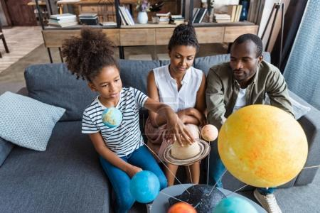 Girl and parents with solar system model
