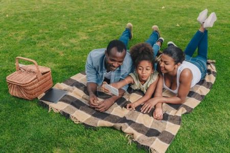 Family taking selfie at picnic