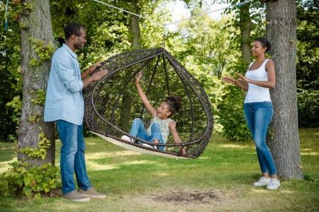 Photo pour Afro-américaine petite fille balancer sur une balançoire avec parents près de parc - image libre de droit