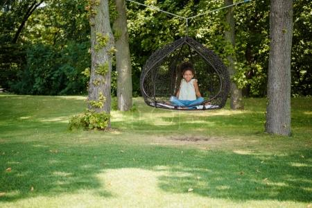 kid swinging on swing in park