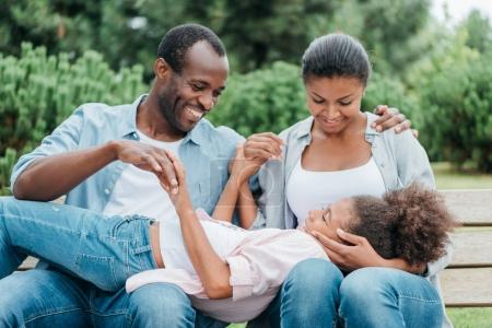 african american family resting on bench