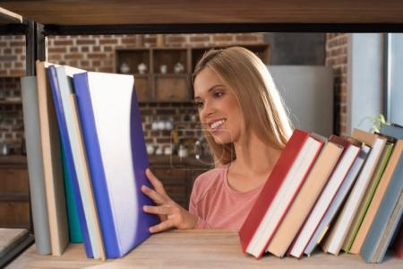 female student looking at books
