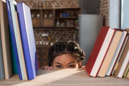 student hiding behind bookshelf