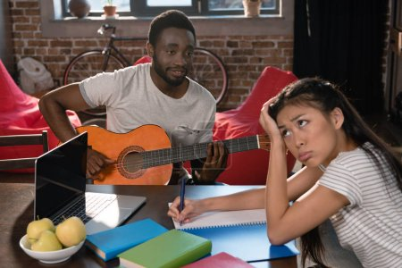 girl studying while student playing guitar