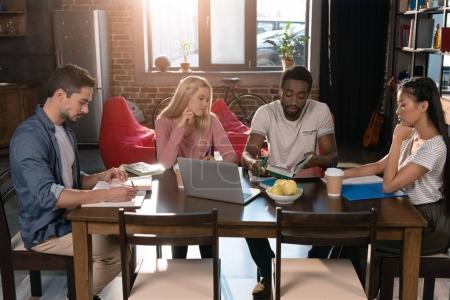 Photo pour Étudiants multiethniques avec ordinateur portable et livres étudient ensemble à la maison - image libre de droit