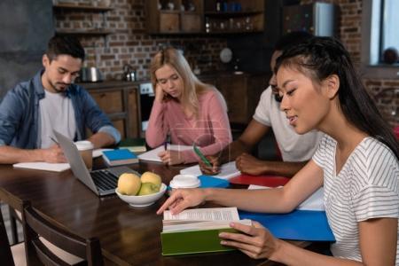 Photo pour Étudiants multiethniques avec ordinateur portable, copybooks et livres étudiant ensemble à la maison - image libre de droit