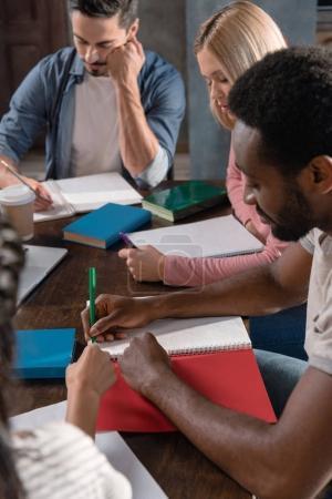 Photo pour Étudiants multiethniques étudiant et écrivant dans des livres à la maison - image libre de droit