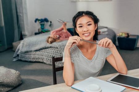 Photo pour Jeune femme asiatique, étudiant à la maison avec son amie pose dans son lit - image libre de droit