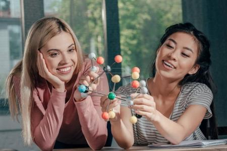 Photo for Young happy women studying with chemistry model - Royalty Free Image