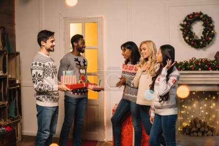 multicultural friends exchanging christmas gifts