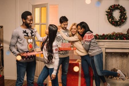 Photo pour Hommes multiculturels présentant des cadeaux de Noël à des amis tout en célébrant des cadeaux ensemble - image libre de droit