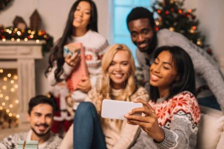Foto de Grupo multiétnico de amigos tomando selfie juntos en smartphone en el país en vísperas de Navidad - Imagen libre de derechos