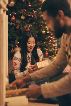 Photo for Selective focus of asian woman looking at christmas gift in hands while boyfriend checking fire in fireplace - Royalty Free Image