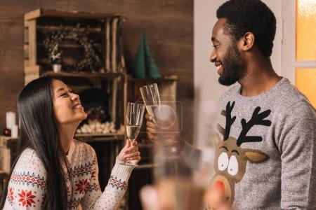 Foto de Ve el lado feliz pareja multicultural f tintineos de copas de champagne durante la celebración de la Navidad - Imagen libre de derechos
