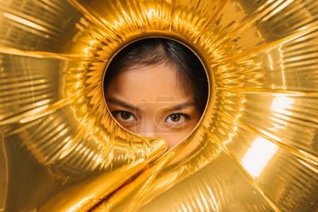 woman looking through balloon