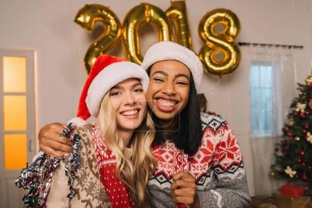 happy multicultural women in santa claus hats