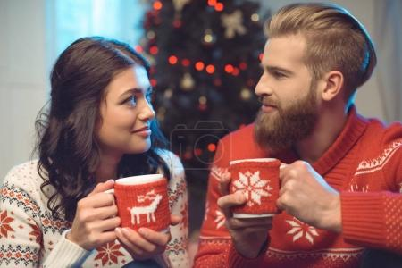 couple with hot drinks on christmas