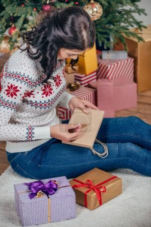 woman unpacking christmas gift