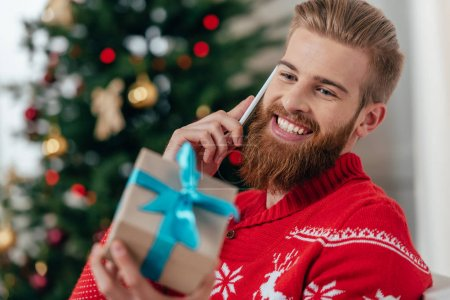 man talking by phone and looking at gift