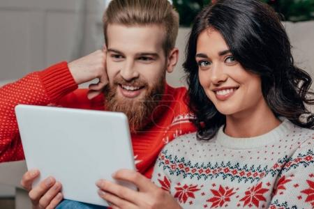 couple in christmas sweaters using tablet